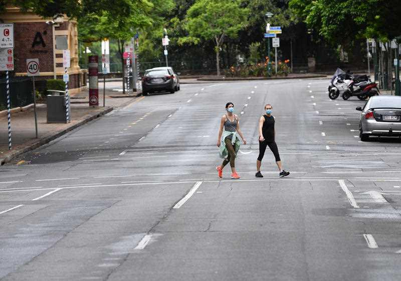 Two women are seen crossing an empty Edward Street in the CBD of Brisbane.