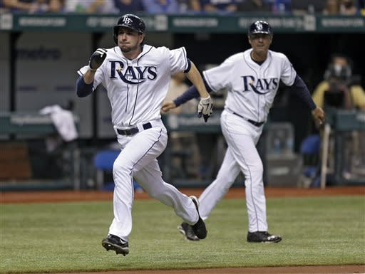 Tampa Bay Rays' Matt Joyce, left, races past third base coach Tom Foley to score on a seventh-inning RBI single by Jose Molina off New York Yankees starting pitcher Phil Hughes during a baseball game Tuesday, April 23, 2013, in St. Petersburg, Fla. (AP Photo/Chris O'Meara)