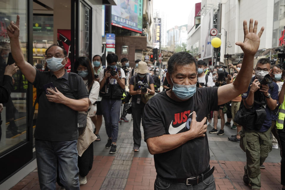 """Protesters raise five fingers, signifying their """"Five demands and not one less"""" as they march in Causeway Bay, Hong Kong, during China's National Day, Thursday, Oct. 1, 2020. A popular shopping district in Causeway Bay saw a heavy police presence the Oct. 1 National Day holiday despite the low protester turnout. (AP Photo/Kin Cheung)"""