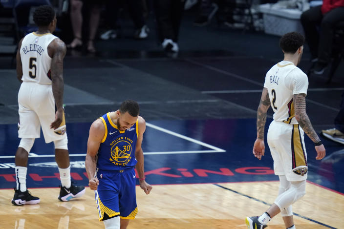 Golden State Warriors guard Stephen Curry (30) reacts after scoring a basket in the second half of an NBA basketball game as New Orleans Pelicans guard Eric Bledsoe (5) and guard Lonzo Ball (2) walk away in New Orleans, Monday, May 3, 2021. The Warriors won 123-108. (AP Photo/Gerald Herbert)