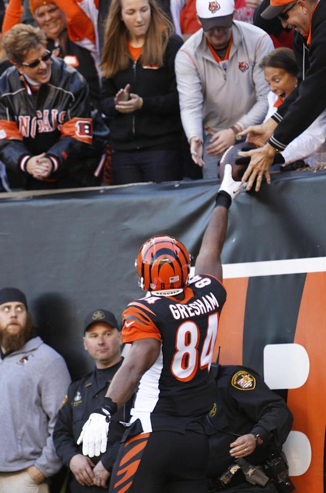 Cincinnati Bengals tight end Jermaine Gresham (84) hands a football to a fan after catching a four-yard touchdown pass in the first half of an NFL football game against the New York Jets, Sunday, Oct. 27, 2013, in Cincinnati. (AP Photo/David Kohl)