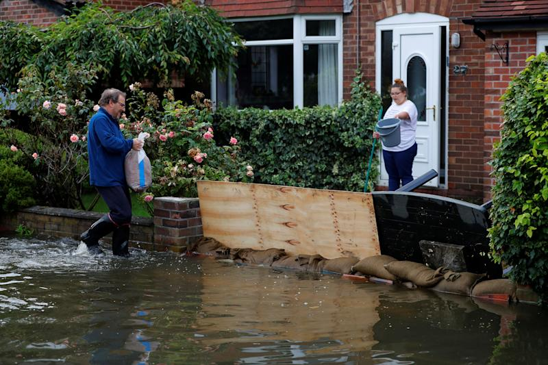 A man tries to board up his drive to prevent rising flood water from entering his house in the Sale area of Manchester, Britain, July 31, 2019. REUTERS/Phil Noble