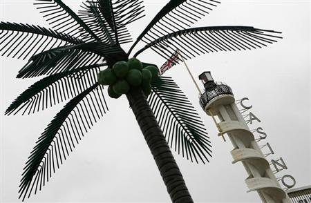 A casino sign stands behind a plastic palm tree in Blackpool