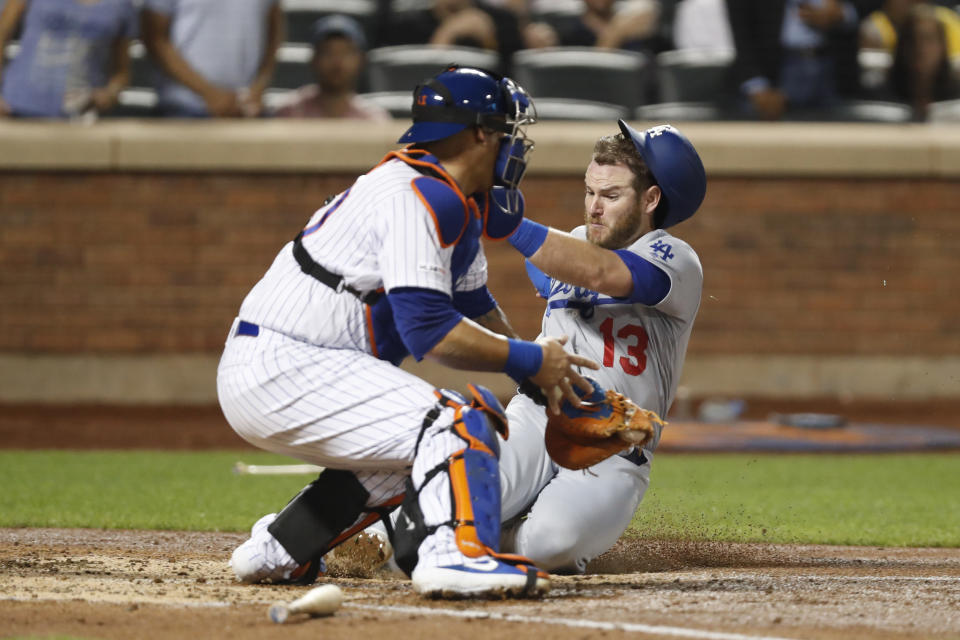 New York Mets catcher Wilson Ramos, left, has the ball in his glove but cannot make the tag in time as Los Angeles Dodgers' Max Muncy (13) scores on Cory Seager's fourth-inning RBI-single in a baseball game Sunday, Sept. 15, 2019, in New York. (AP Photo/Kathy Willens)