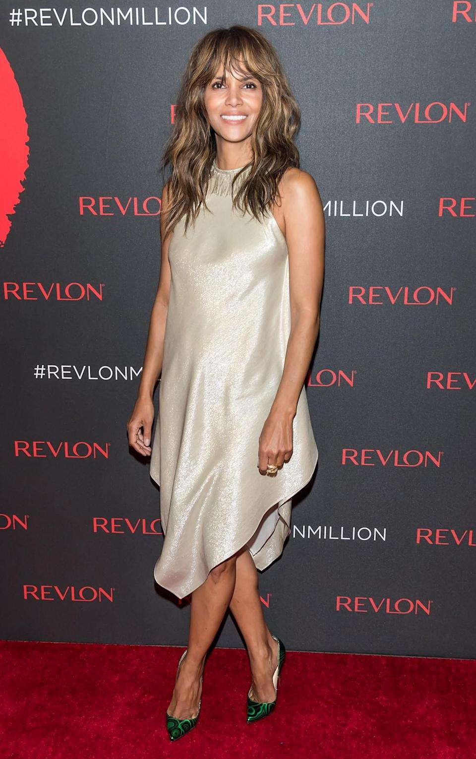 <p>Wearing a dress almost identical to Kendall's slinky slip dress, Halle proves that a woman of 50 can absolutely rock this look. [Photo: Getty] </p>