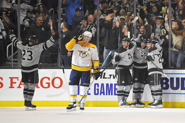 Members of the Los Angeles Kings, right, celebrate a goal by left wing Alex Iafallo as Nashville Predators center Ryan Johansen skates away during the third period of an NHL hockey game Saturday, Oct. 12, 2019, in Los Angeles. The Kings won 7-4. (AP Photo/Mark J. Terrill)