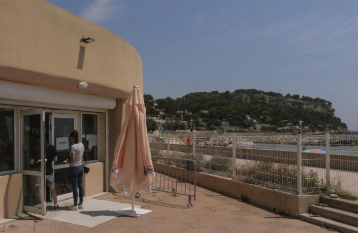 FILE - In this Friday, July 23, 2021, file photo, people enter a vaccination center at the beach in Carry-le-Rouet, southern France. Europe's famed summer holiday season is in full swing, but efforts to inoculate people against coronavirus are not taking a break. From France's Mediterranean coast to Italy's Adriatic beaches, health authorities are trying to make a COVID-19 shot as much a part of this summer as sunscreen and shades.(AP Photo/Nicolas Garriga, File)