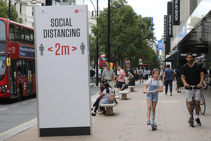 A social distancing sign telling people to adhere to social distancing and stay two metres apart on Oxford Street, London. (PA)