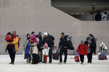 Migrants carry their belongings as they leave the Tae Kwon Do stadium at the southern suburb of Faliro in Athens
