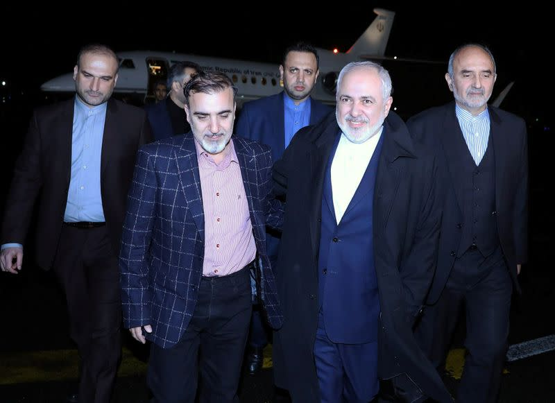 Iran's Foreign Minister Mohammad Javad Zarif walks with Iranian professor Massoud Soleimani as he arrives at Mehrabad airport, in Tehran