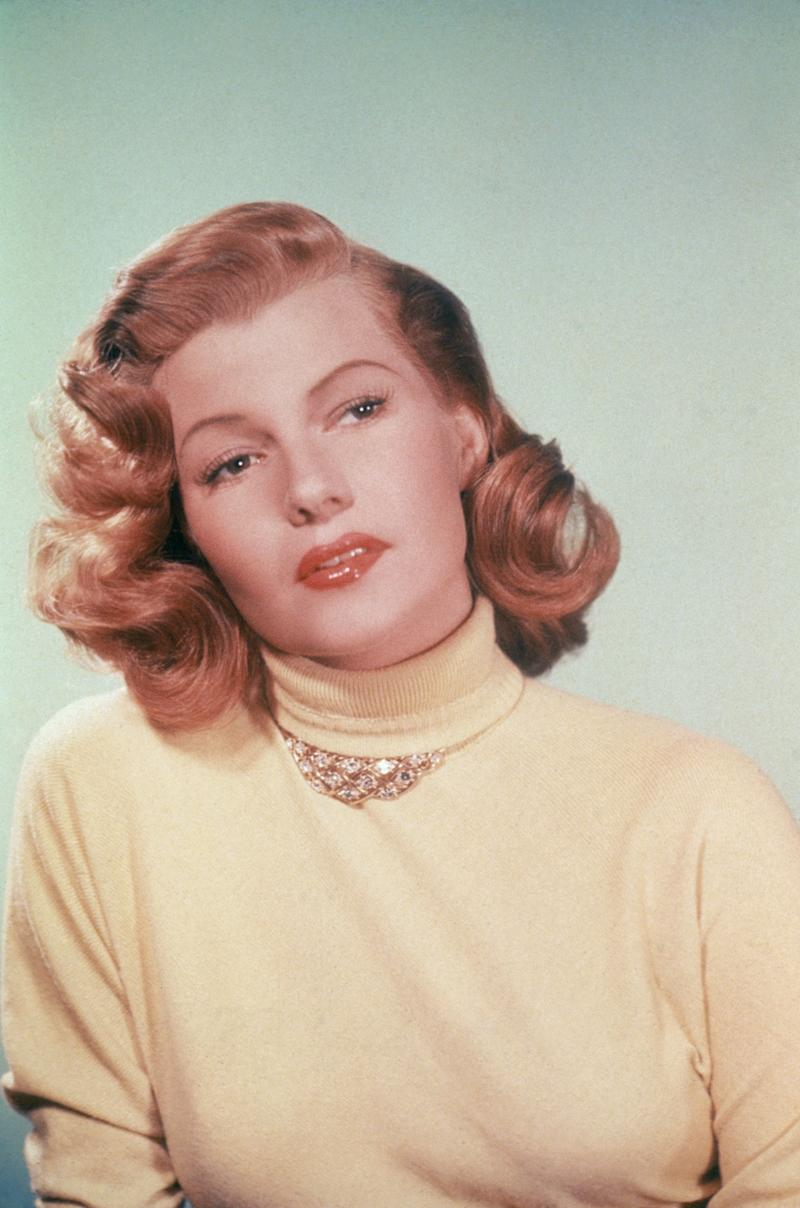 The actress wears a yellow turtleneck, circa 1950.