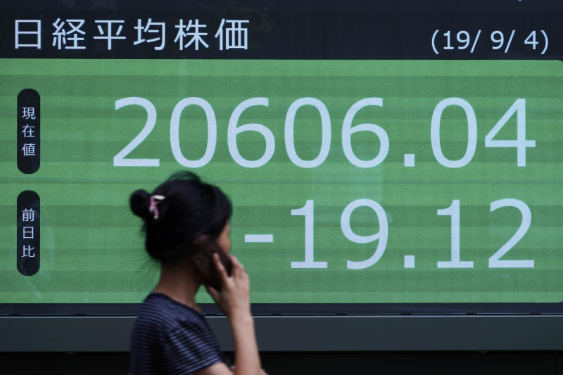 A woman walks past an electronic stock board showing Japan's Nikkei 225 index at a securities firm in Tokyo Wednesday, Sept. 4, 2019. Asian stock markets rose Wednesday following surprise weakness in U.S. manufacturing and wrangling in Britain over the country's departure from the European Union. (AP Photo/Eugene Hoshiko)