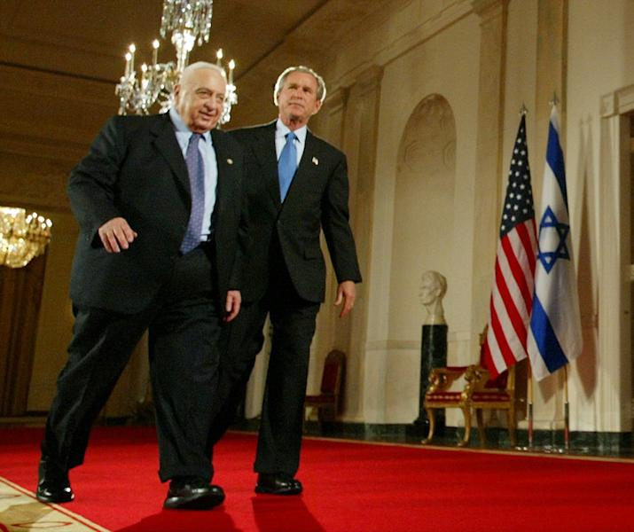 """FILE - In this Wednesday, April 14, 2004 file photo, President Bush, right, and Israeli Prime Minister Ariel Sharon, left, walk together at the end of a joint press conference in the Cross Hall of the White House in Washington. The son of former Israeli Prime Minister Ariel Sharon says his father has died on Saturday, Jan. 11, 2014. The 85-year-old Sharon had been in a coma since a debilitating stroke eight years ago. His son Gilad Sharon said: """"He has gone. He went when he decided to go."""" (AP Photo/Pablo Martinez Monsivais, File)"""