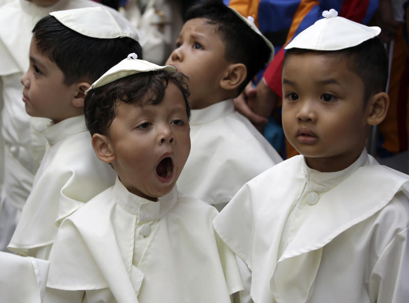 A boy dressed as a Pope, yawns as he prepares to join a parade in celebration of the canonization or the elevation to sainthood in the Vatican of Roman Catholic Pope John Paul II and Pope John XXIII Sunday, April 27, 2014, at suburban Quezon city, northeast of Manila, Philippines. Pope Francis declared his two predecessors John XXIII and John Paul II saints on Sunday before hundreds of thousands of people in St. Peter's Square, an unprecedented ceremony made even more historic by the presence of retired Pope Benedict XVI. The predominantly Roman Catholic Philippines joins several nations worldwide in the celebration of canonization of the two Popes. (AP Photo/Bullit Marquez)