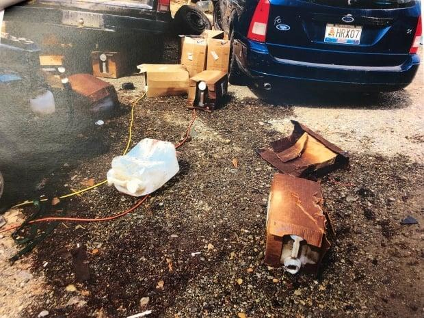 A 2018 photo of a lot in Whitehorse's McRae neighbourhood covered with old vehicles and plastic jugs containing used cooking oil. A trial for the property's owner, who is charged with violations of Yukon's Wildlife Act, took place last week. (Court exhibit - image credit)
