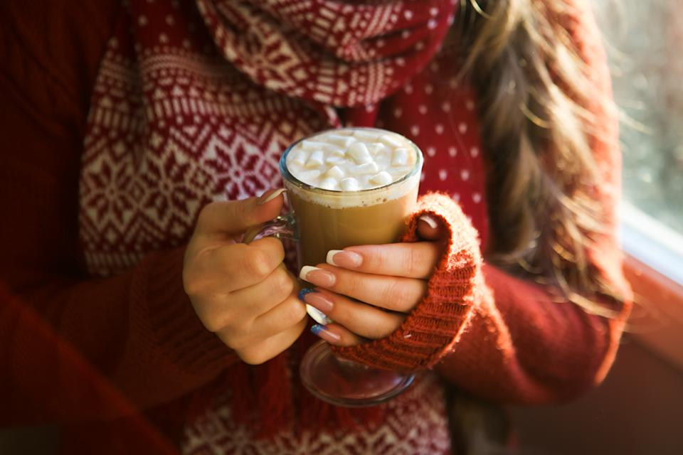 beautiful happy woman drinking cup of coffee sitting home by the window. Christmas morning. Christmas drink