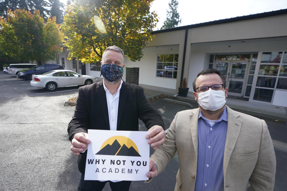 Garth Reeves, left, and Scott Canfield, co-founders of the Why Not You Academy charter school, pose for a photo with the school's new name and logo, Tuesday, Oct. 27, 2020, in front of the building that will house the school in Des Moines, Wash., south of Seattle. Seattle Seahawks NFL football quarterback Russell Wilson and his Grammy-winning wife, pop singer Ciara, are putting their money and celebrity behind rebranding the charter school, which advocates hope will boost the troubled Washington state charter school sector that has suffered from enrollment problems after years of legal challenges. (AP Photo/Ted S. Warren)