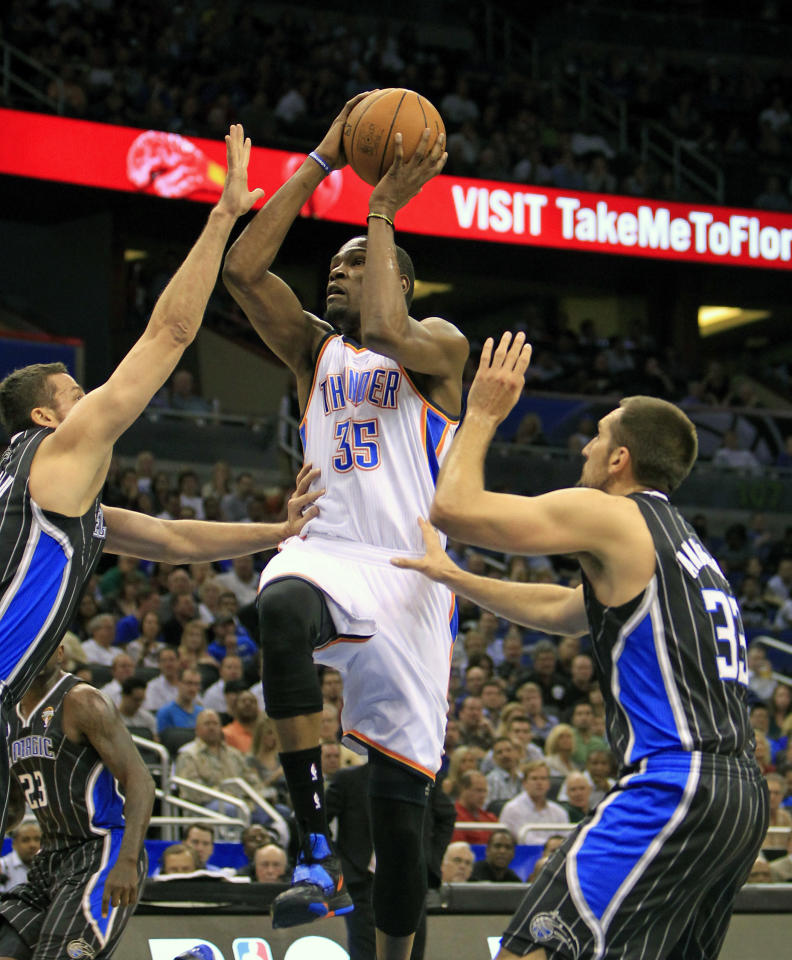 Oklahoma City Thunder's Kevin Durant (35) gets off a shot between Orlando Magic's Hedo Turkoglu, left, and Ryan Anderson (33) during the first half of an NBA basketball game on Thursday, March 1, 2012, in Orlando, Fla. (AP Photo/John Raoux)