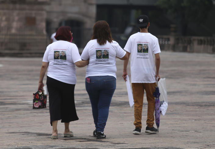 Family members wear T-shirts with photos of disappeared Jorge Arevelo and Ricardo Valdes, during a protest in Monterrey, Nuevo Leon state, Mexico, Thursday, June 24, 2021. As many as 50 people in Mexico are missing after they set off on simple highway trips between the industrial hub of Monterrey and the border city of Nuevo Laredo; relatives say they simply disappeared on the heavily traveled road, which has been dubbed 'the highway of death,' never to be seen again. (AP Photo/Roberto Martinez)