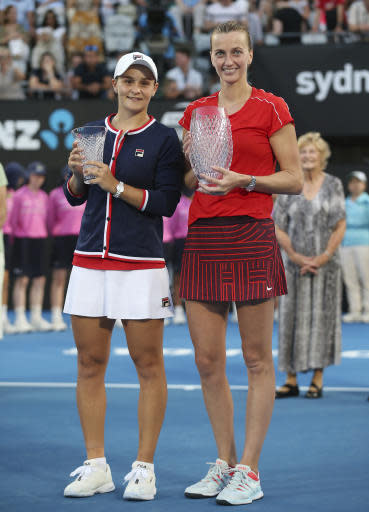 Petra Kvitova of the Czech Republic, right, holds the winners trophy as she poses for photographers with runner up Ashleigh Barty of Australia after their women's final match at the Sydney International tennis tournament in Sydney, Australia, Saturday, Jan. 12, 2019. (AP Photo/David Moir)