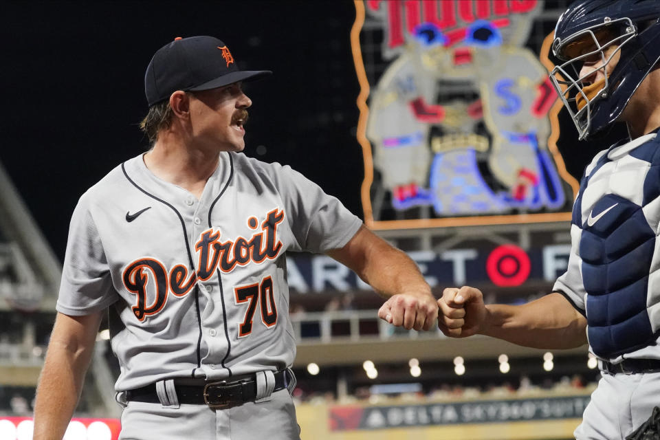 Detroit Tigers pitcher Tyler Alexander, left, gets a fist-bump from catcher Dustin Garneau after the sixth inning of a baseball game against the Minnesota Twins, Tuesday, Sept. 28, 2021, in Minneapolis. (AP Photo/Jim Mone)