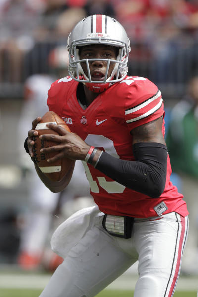 FILE - In this Sept. 21, 2013 file photo, Ohio State quarterback Kenny Guiton looks for a receiver against Florida A&M during an NCAA college football game in Columbus, Ohio. Guiton is coming off three terrific games with Braxton Miller out, but head coach Urban Meyer has said that if Miller is healthy enough and has a good week of practice, he'll be the first one to take a snap from center on Saturday night against Wisconsin. (AP Photo/Jay LaPrete, File)