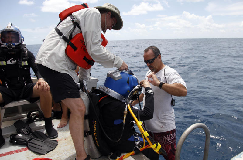 "Sylvia Earle, center, puts on her helmet as Dale Stokes, left, and Roger Garcia, right, assist before a dive to the undersea research laboratory Aquarius Reef Base, Friday, July 13, 2012, in the Florida Keys. IN 1970, Earle led the first team of women ""aquanauts"" to the lab several miles off Key Largo. NOAA owns the lab that has rested for decades some 60 feet below the water's surface on the Conch Reef in the Florida Keys National Marine Sanctuary. But federal budget cuts threaten to close the undersea lab unless it can secure private funding. (AP Photo/Lynne Sladky)"
