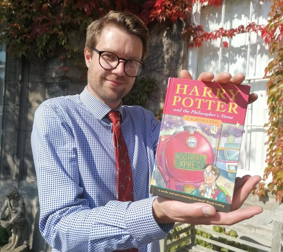 Books expert Jim Spencer with a first edition hardback copy of Harry Potter and the Philosopher's Stone. Image: Hansons Auctions.