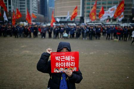 A member of Korean Confederation of Trade Unions holds a placard while chanting slogans during a general strike calling for South Korean President Park Geun-hye to step down, in central Seoul, South Korea November 30, 2016. REUTERS/Kim Hong-Ji