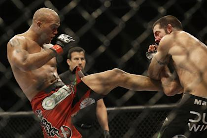 Robbie Lawler, left, kicks Matt Brown during the fifth round of their welterweight fight. (AP)
