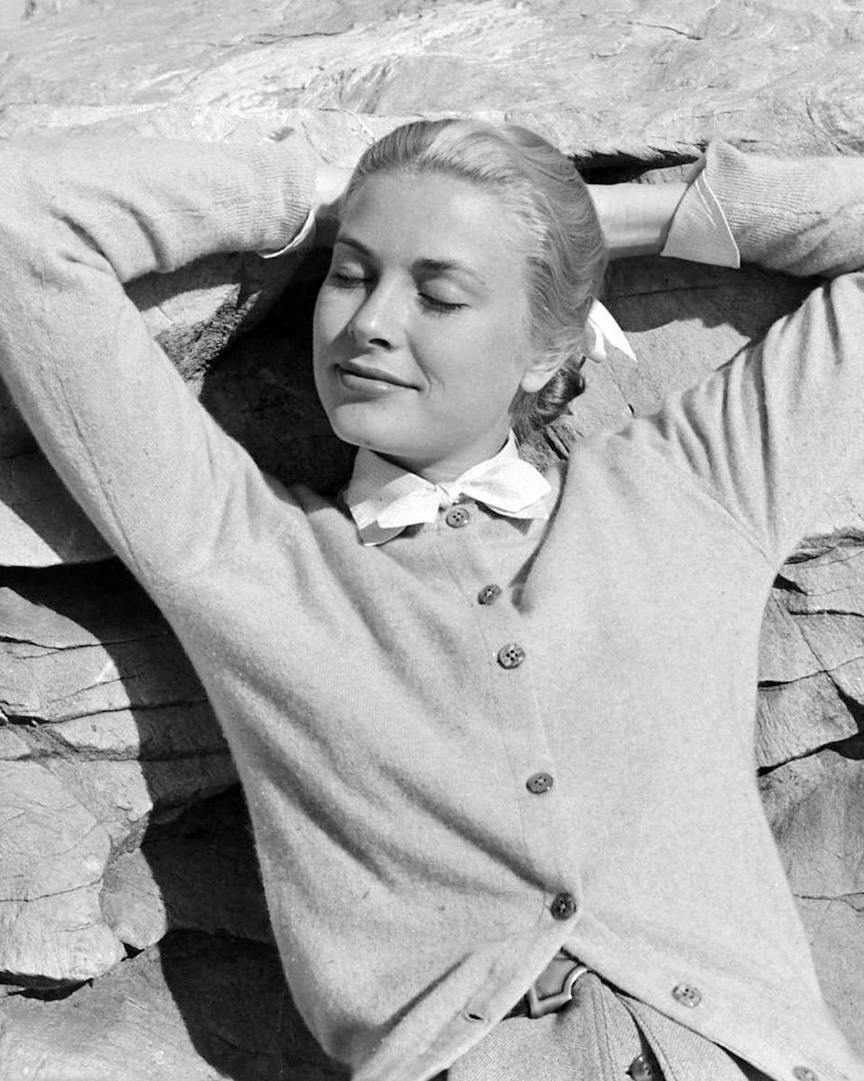 <p>While Kelly was known for her red carpet glamour, she could typically be found in casual clothing when she was off-duty. Here, the actress reclines on a rock wearing a cardigan sweater with a bow collar. </p>