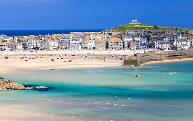 Revisit an old favourite this summer, suggests Gill Charlton, our Cornwall expert. You'll find Scandi style, picturesque hiking routes and the best burgers in Britain. Go now The quality of the summer light in St Ives has inspired generations of artists. Tate St Ives has doubled in size and a major Patrick Heron retrospective has just opened. For a quieter time and to enjoy the cultural side of the resort, visit before mid-July when the bucket-and-spade crowds arrive. Travel down by train (gwr.com) or leave your car at Lelant Saltings and ride the branch line around the bay. St Ives - City map Stay here Lovers of Scandi style will delight in Trevose Harbour House (2) (trevosehouse.co.uk), a few steps from the harbour. Doubles cost from £165 including breakfast. Rather cheaper and offering a particularly warm welcome as well as panoramic sea views, West by Five (1) (westbyfive.com) is the best B&B in town. Doubles cost from £120, including breakfast. Walk the coast path from St Ives to Zenno Credit: istock Walk here You can, of course, simply wander the alleys of the Downalong area or stroll along the harbour front and town beaches. But if you are feeling energetic, take the coastal path to Zennor, a three-hour hike along the cliffs. Look out for seals on the offshore Carracks (rocky islands). Reward yourself with a pint at the medieval Tinners Arms before catching the bus back. Try a spot of surfing Credit: istock See this Tate St Ives (3) (tate.org.uk) has a superbly curated permanent exhibition of works by leading 20th century St Ives artists. The new galleries will display Patrick Heron's glorious vibrant abstracts until Sept 30. Entry £9.50. Tate St Ives Credit: 2017 Getty Images/Matt Cardy Try this The gentle swell that rolls on to Porthmeor Beach just below Tate makes it ideal for learning to surf. St Ives Surf School (4) (stivessurfschool.co.uk) offers lessons for all levels. Pub walks | Routes that start and end at a characterful inn Shop here Fore Street (5) has the best of the resort's many art galleries and leisure clothes shops. For studio ceramics visit St Ives Ceramics (6) (st-ives-ceramics.co.uk) in Fish Street. For unusual gifts and exotic jewellery head for Sweet Lime (7) (sweetlimeuk.com) on Wills Lane. Drink here Porthmeor Café (8) (porthmeor-beach.co.uk) has an open-air cocktail bar with a grandstand view of surfers in action. Try the basil bramble fizz (£7.50) or split a jug of sangria (£15). The best hotels in Cornwall Eat here Beachside Porthminster Café (9) (porthminstercafe.co.uk) wins accolades for its modern take on fish and seafood classics, as well as its picture-postcard view of the harbour; around £40 per person including wine. Alternatively, Blas (10) (blasburgerworks.co.uk) in the Warren serves possibly the best burgers in Britain. Join the locals at West on Porthmeor Beach (5) for a superb stone-baked pizza May-September. St Michael's Mount Off the map Take the bus to Marazion and – at low tide – walk across to St Michael's Mount (stmichaelsmount.co.uk) and its colourful gardens, which are at their best in June. At high tide, the mount is cut off by the sea, but a small ferry will run you across for £2. Entry £15, closed Saturdays.