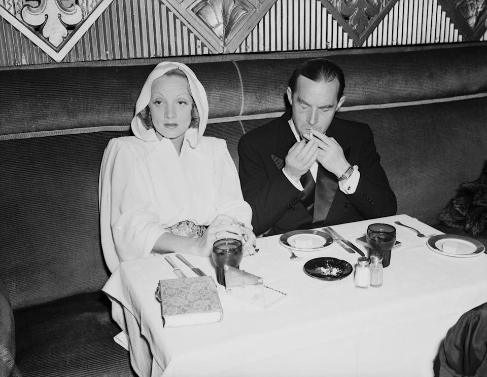 <p>Dietrich and Erich Maria Remarque, one of her many lovers, attend the premiere of the film <em>Juarez</em> in Los Angeles. Dietrich wears a hooded dress, looking the part of mysterious and trend-setting starlet. <br></p>