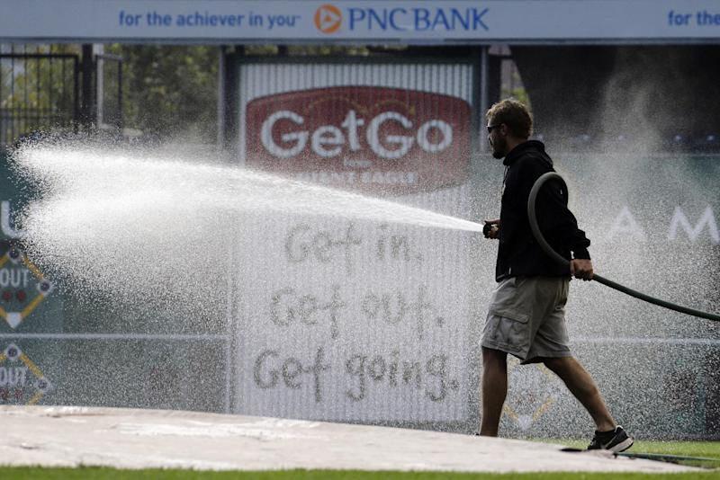 A member of the PNC Park ground crew waters the infield before baseball workouts in Pittsburgh, Saturday, Oct. 5, 2013. The Pittsburgh Pirates are scheduled to play the St. Louis Cardinals in Game 3 of the National League division series on Sunday. (AP Photo/Gene J. Puskar)