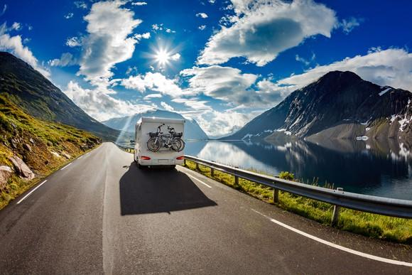 A camper van with bikes attached to the back driving down a beautiful scenic road.