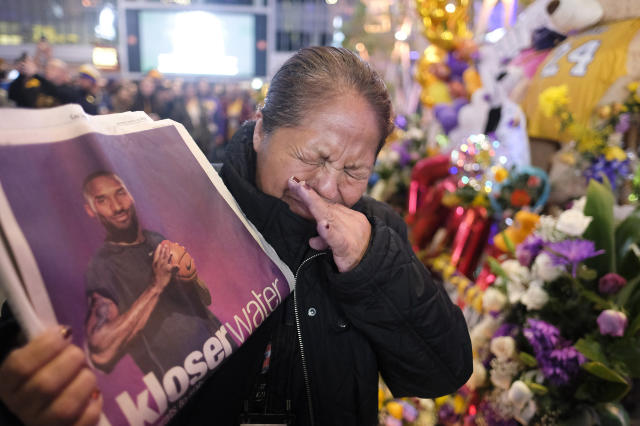 Ana Sebastian, from Guatemala, shows a copy of newspaper with a picture of the late Kobe Bryant at a memorial for Bryant near Staples Center, Monday, Jan. 27, 2020, in Los Angeles. Bryant, the 18-time NBA All-Star who won five championships and became one of the greatest basketball players of his generation during a 20-year career with the Los Angeles Lakers, died in a helicopter crash Sunday. (AP Photo/Ringo H.W. Chiu)