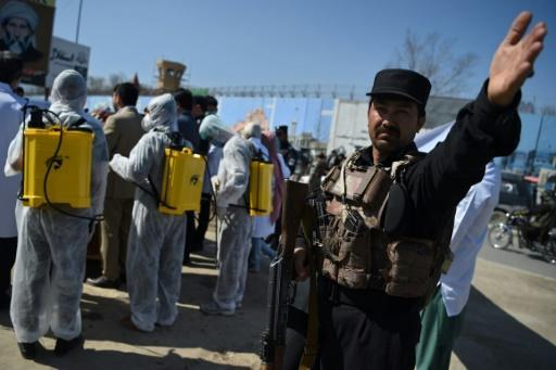 An Afghan policeman gestures as volunteers wearing a hazmat suits and a facemasks gather before the start of a preventive campaign against the spread of the COVID-19 coronavirus, in Kabul on March 18, 2020
