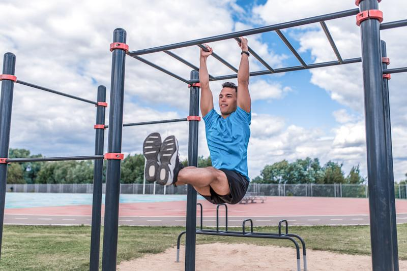 Athlete man pulls himself from crossbar in summer in city morning exercise, press exercise, twisting legs to crossbar, grass cloud background. Active youth lifestyle, fitness workout man