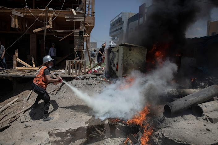 A Palestinian firefighter extinguishes a fire May 17 at a beachside cafe hit by an Israeli airstrike in Gaza City.