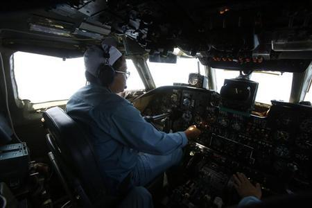 Caption Dinh Van Qua operates on the cockpit of an aircraft AN-26 belonging to the Vietnam Air Force during a search and rescue mission off Vietnam's Tho Chu island