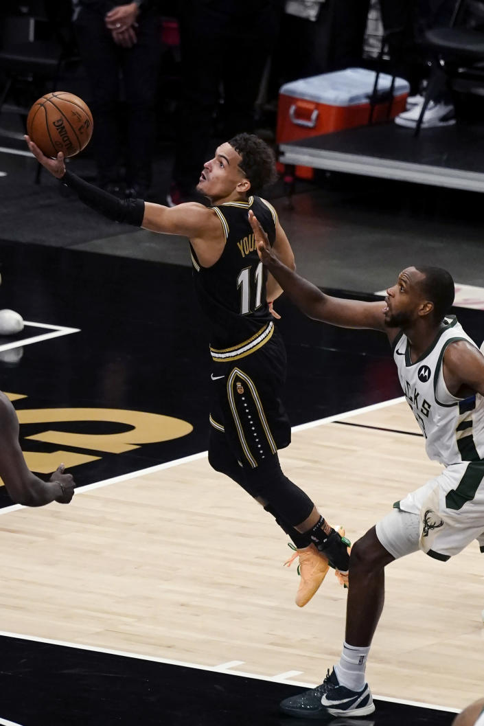 Atlanta Hawks guard Trae Young (11) shoots next to Milwaukee Bucks forward Khris Middleton (22) during the second half of Game 6 of the Eastern Conference finals in the NBA basketball playoffs Saturday, July 3, 2021, in Atlanta. (AP Photo/John Bazemore)