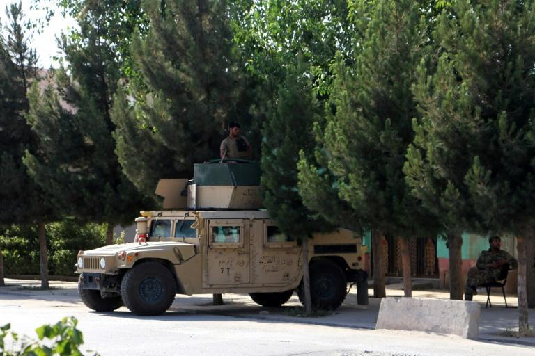 Afghan security forces stand guard along a road in Kunduz on June 22, 2021