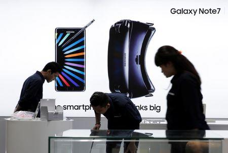 Sales promotion staff stand in front of Galaxy Note 7 advertisement at Samsung store in Jakarta