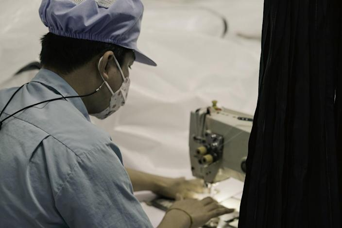 A worker at a sewing machine at a factory in Thailand