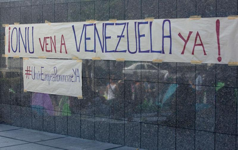 "A banners is posted on the wall of the United Nations offices in Caracas, Venezuela, Tuesday, March 25, 2014. The banners reads in Spanish ""UN come to Venezuela now"" and the one below reads ""European Union pronounce yourself"". A large group of protesting anti-government students have camped in front of the office of the United Nations asking it to come and observe the situation, as Venezuela's bloody political standoff heads into its third month. The decision to pitch tents on the concrete sidewalk along one of Caracas' busiest, smog-filled streets comes as foreign ministers from several South American nations arrive Tuesday to lend support to President Nicolas Maduro's efforts at reconciliation with his opponents. (AP Photo/Fernando Llano)"