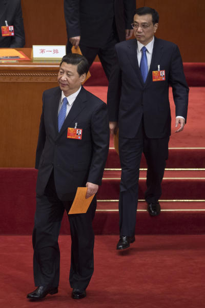 Chinese President Xi Jinping, front, and Premier Li Kiqiang, back, walks to a ballot box to cast their votes during a plenary session of the NPC in Beijing's Great Hall of the People, China, Saturday, March 16, 2013. China's new leaders turned Saturday to veteran technocrats with greater international experience to staff a Cabinet charged with overhauling a slowing economy and pursuing a higher global profile without triggering opposition. (AP Photo/Alexander F. Yuan)