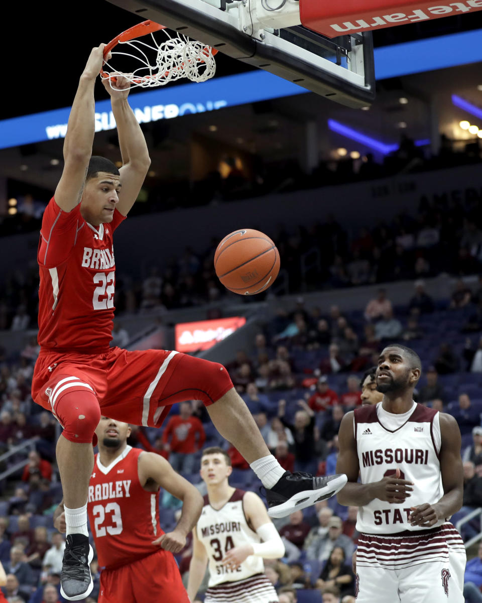 Bradley's Ja'Shon Henry (22) dunks as Missouri State's Josh Webster, right, watches during the second half of an NCAA college basketball game in the quarterfinal round of the Missouri Valley Conference tournament, Friday, March 8, 2019, in St. Louis. Bradley won 61-58. (AP Photo/Jeff Roberson)