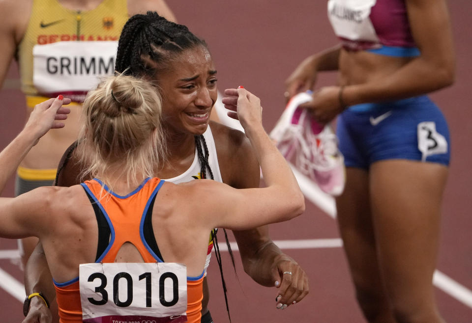 Nafissatou Thiam, of Belgium is greeted by Anouk Vetter, of Netherlands, silver, after winning the gold medal in the heptathlon at the 2020 Summer Olympics, Thursday, Aug. 5, 2021, in Tokyo, Japan. (AP Photo/Charlie Riedel)