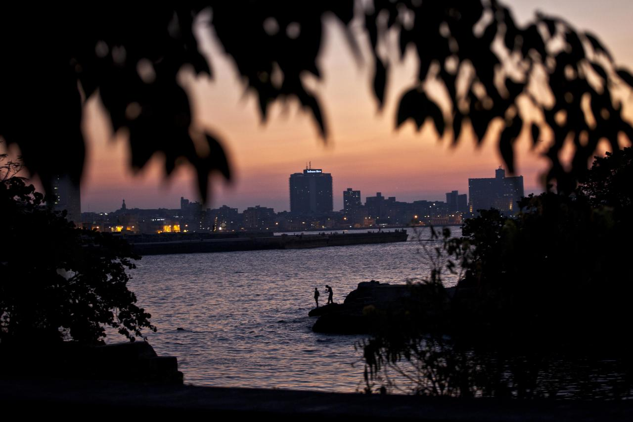 In this picture taken Sept 10, 2012, two people watch the sunset from the bay in Havana, Cuba. When the Obama administration loosened travel restrictions to Cuba, the thought was that Americans were going to pour into the island on legal cultural exchanges. But several U.S. travel operators complain that, just over a year after the U.S. re-instituted so-called people-to-people exchanges to Cuba, applications to renew their licenses are languishing, forcing cancellations, layoffs and the loss of millions of dollars in revenue. (AP Photo/Ramon Espinosa)
