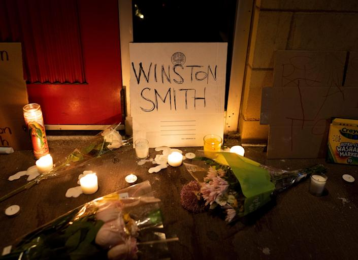 Candles and flowers are arranged at a vigil for Winston Boogie Smith Jr. early on Saturday, June 5, 2021. Authorities say Smith, wanted on a weapons violation, fired a gun from inside his vehicle before he was fatally shot by members of a federal task force as they were trying to arrest him.